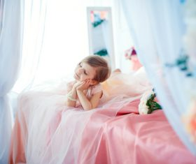 Dressed up beautiful little girl sitting on the bed Stock Photo 06