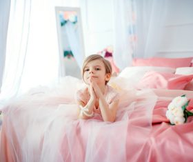 Dressed up beautiful little girl sitting on the bed Stock Photo 07