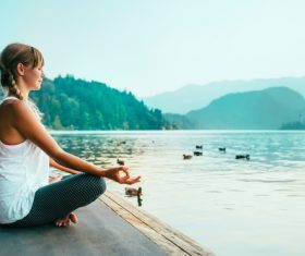 Early morning woman practicing yoga by the lake Stock Photo 10