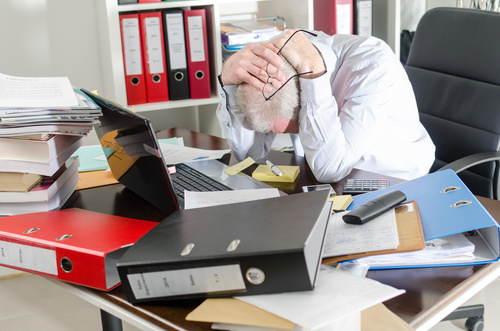 Exhausted man with excessive work pressure Stock Photo