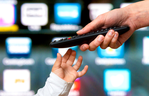 Father gives remote control to son Stock Photo