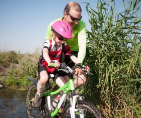 Father pushes bicycle to help children cross the river Stock Photo
