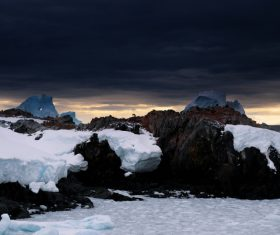 Frozen ice on rocky beach in winter Stock Photo