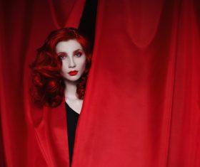 Girl hiding in red drapery Stock Photo