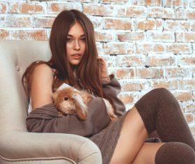 Girl holding pet sitting on the sofa Stock Photo