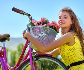 Girl hugs car basket of flowers Stock Photo