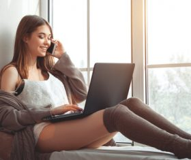 Girl sitting on the window sill and answering the phone Stock Photo