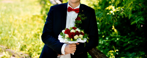 Groom holding bouquet of flowers Stock Photo