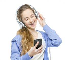 Happy girl listening to music with mobile phone Stock Photo