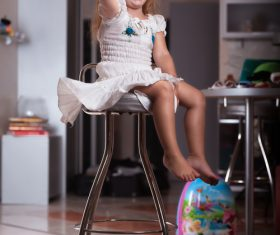 Happy little girl sitting on a metal chair Stock Photo