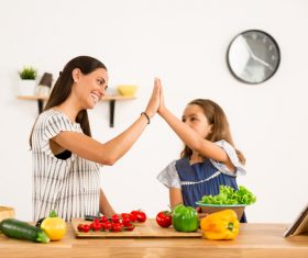 Happy mother and daughter in the kitchen clap Stock Photo