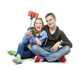 Happy teen boy and girl using a smartphone selfie Stock Photo 02