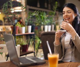 Lady eating afternoon tea looking at computer video Stock Photo