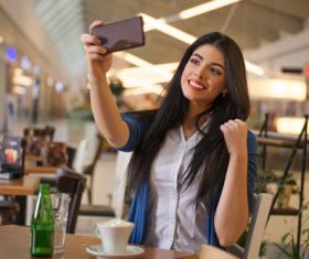 Lady using a smartphone to take selfie Stock Photo