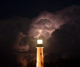 Lighthouse and lightning in cumulonimbus Stock Photo