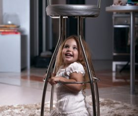 Little girl hiding under metal chair Stock Photo