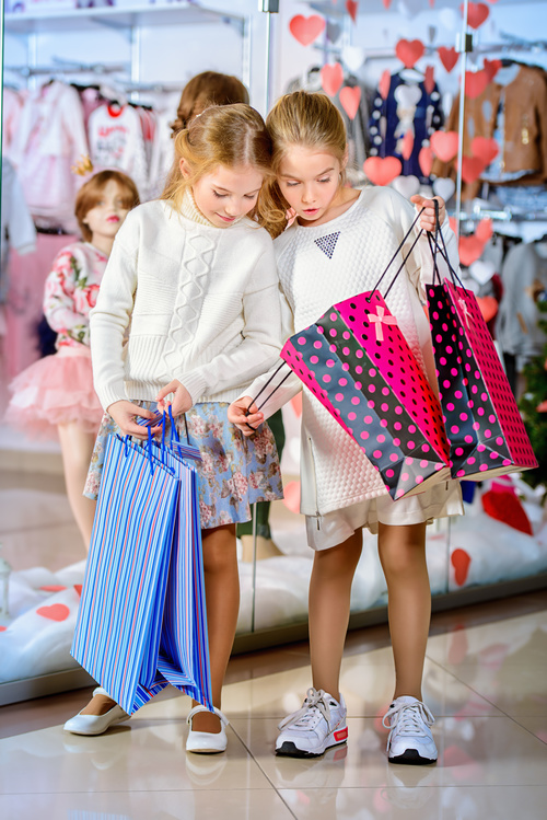 Little girl looking at what is in the shopping bag Stock Photo