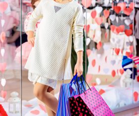 Little girl posing holding a shopping bag in front of the mirror Stock Photo 01