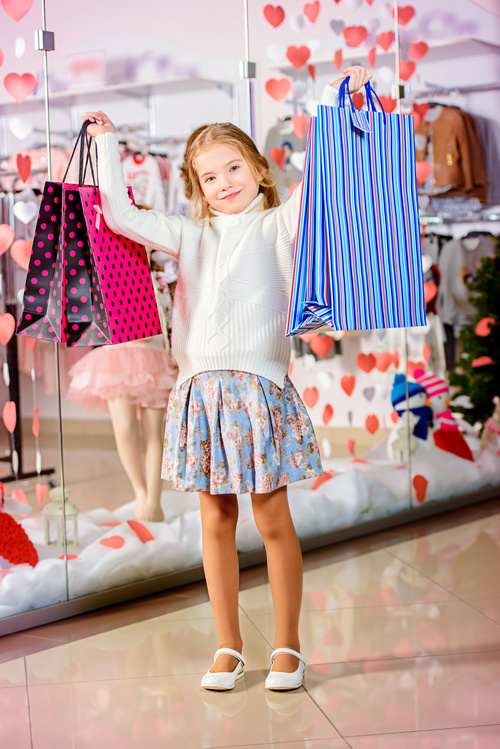 Little girl posing holding a shopping bag in front of the mirror Stock Photo 02