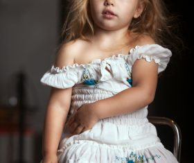 Little girl sitting on metal chair Stock Photo