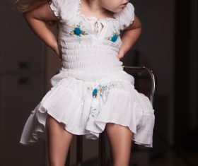 Little girl wearing moms high heels sitting on metal chair Stock Photo 02