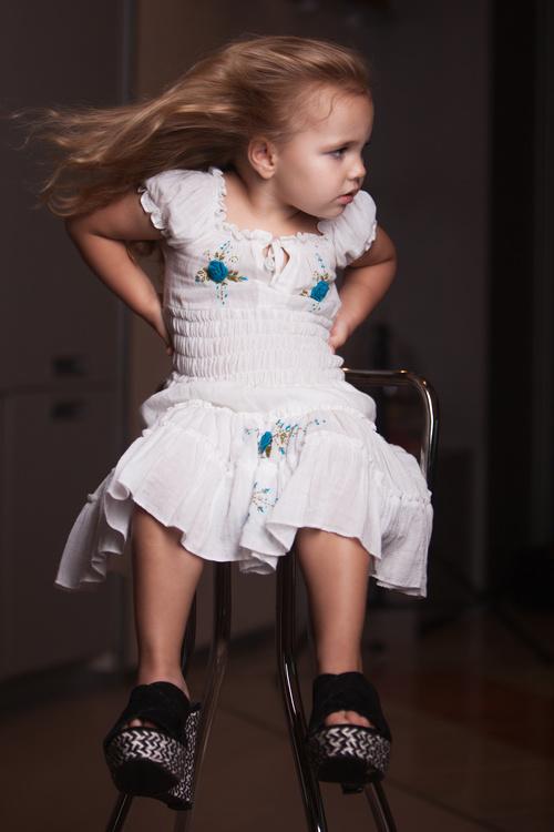 Little Girl Wearing Moms High Heels Sitting On Metal Chair