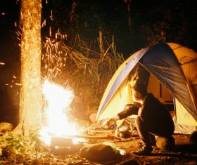 Man camping ignites campfire Stock Photo