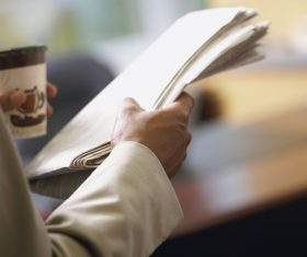 Man drinking coffee and reading newspaper Stock Photo