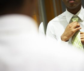 Man with a tie in front of the mirror Stock Photo