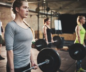 Men and women doing barbell exercises in the gym Stock Photo 01