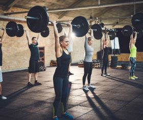 Men and women doing barbell exercises in the gym Stock Photo 02