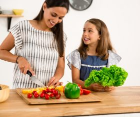 Mom teach her daughter cutting vegetables in the kitchen Stock Photo 01