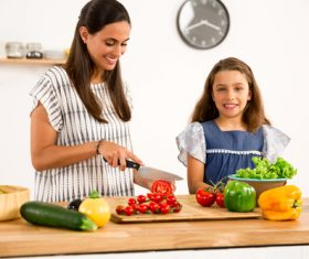 Mom teach her daughter cutting vegetables in the kitchen Stock Photo 02