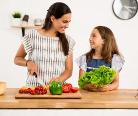 Mom teach her daughter cutting vegetables in the kitchen Stock Photo 03