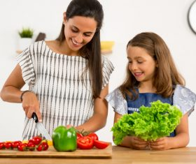 Mom teach her daughter cutting vegetables in the kitchen Stock Photo 04