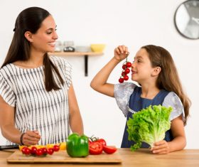 Mom teaches daughter to know vegetables Stock Photo