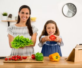Mother and daughter holding fresh vegetables Stock Photo