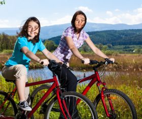 Mother and daughter riding bicycle Stock Photo