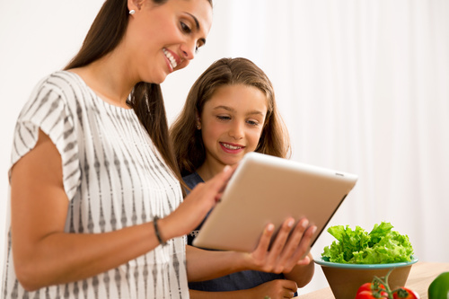 Mother and daughter watch video learn how to cook Stock Photo 01
