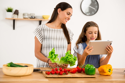 Mother and daughter watch video learn how to cook Stock Photo 02