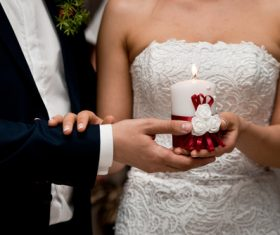 Newlyweds holding candles in hand Stock Photo