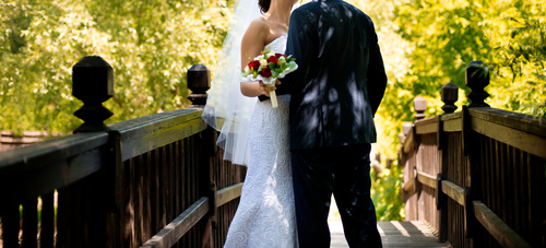 Newlyweds standing on bridge and taking wedding photographs Stock Photo 01