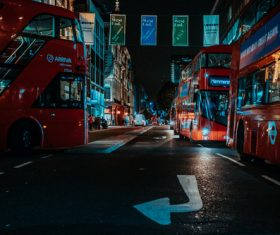 Red buses on urban city at night Stock Photo