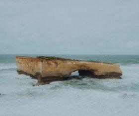 Rock terrain on white wavy beach Stock Photo