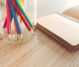 Sharp pencils and a notebook on a table Stock Photo