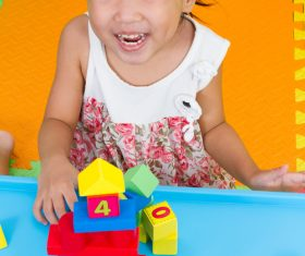 Smiling little girl playing with building blocks Stock Photo