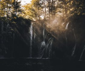 Sun rays on wild waterfall scenery Stock Photo