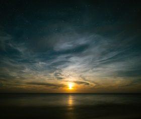 Sunlight on calm beach at dusk Stock Photo