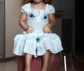 Super cute little girl sitting in chair Stock Photo