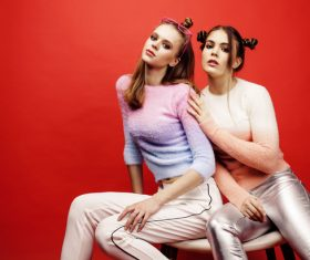 Two fashion hairstyle girls taking pictures in the studio Stock Photo 02